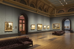 Gallery 34 with Turners hanging on the wall from left to right: NG524, NG508, NG1991, NG538 and NG472.  To the left is Constable's NG130. In the foreground are sofas and wrought iron air vents in the floor.